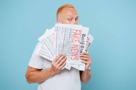 Photo pour Bel homme effrayé tenant des journaux avec de fausses nouvelles, isolé sur bleu - image libre de droit