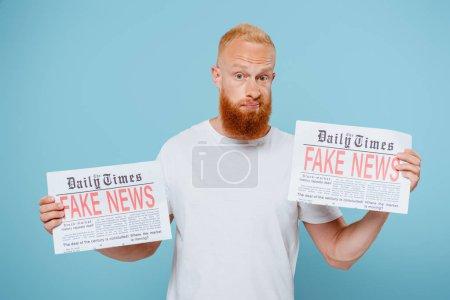 Photo pour Homme barbu confus tenant deux journaux avec de fausses nouvelles, isolé sur bleu - image libre de droit
