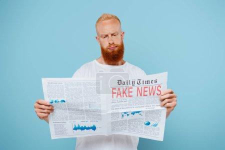 Photo pour Homme barbu sceptique lecture journal avec de fausses nouvelles, isolé sur bleu - image libre de droit