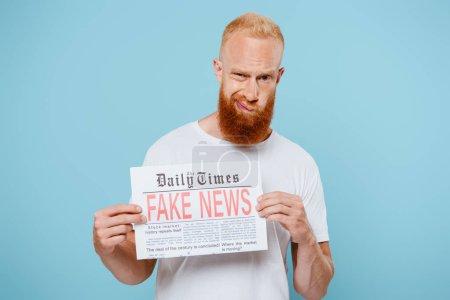 Photo pour Homme barbu sceptique montrant un journal avec de fausses nouvelles, isolé en bleu - image libre de droit