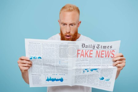 Photo for Shocked bearded man reading newspaper with fake news, isolated on blue - Royalty Free Image