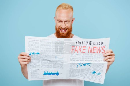 Photo for Cheerful bearded man reading newspaper with fake news, isolated on blue - Royalty Free Image