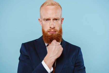 Photo for Handsome bearded thoughtful businessman in suit, isolated on blue - Royalty Free Image