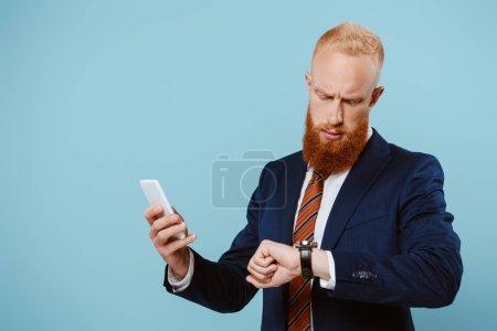 Photo pour Sérieux homme d'affaires barbu à l'aide d'un smartphone tout en regardant montre-bracelet, isolé sur bleu - image libre de droit