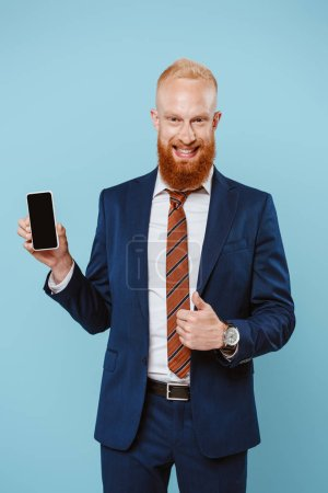 smiling bearded businessman showing thumb up and smartphone with blank screen, isolated on blue