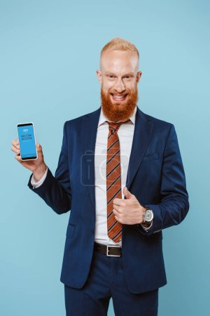 Photo pour KYIV, UKRAINE - 27 AOÛT 2019 : homme d'affaires barbu souriant montrant pouce levé et smartphone avec application Skype, isolé sur bleu - image libre de droit