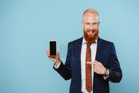 Photo for Smiling bearded businessman pointing at smartphone with blank screen, isolated on blue - Royalty Free Image
