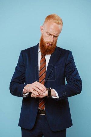 Photo pour Homme d'affaires pensif barbu en costume regardant la montre, isolé sur bleu - image libre de droit