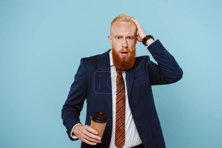 worried bearded businessman holding coffee to go, isolated on blue