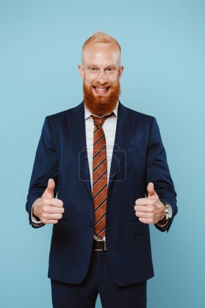 Photo for Smiling bearded businessman in suit showing thumbs up, isolated on blue - Royalty Free Image
