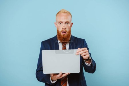 Foto de Sorprendido hombre de negocios barbudo en traje usando el ordenador portátil, aislado en azul - Imagen libre de derechos