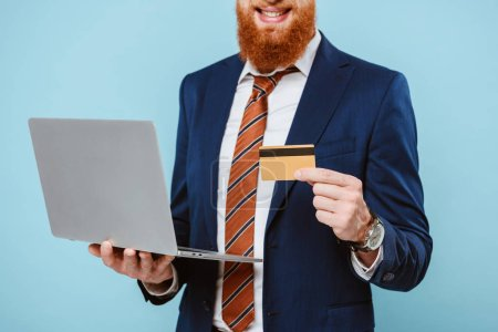 Photo for Cropped view of smiling bearded businessman in suit shopping online with credit card and laptop, isolated on blue - Royalty Free Image