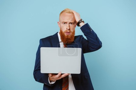 worried bearded businessman in suit using laptop, isolated on blue