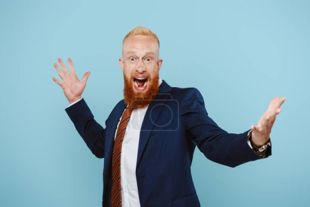 Photo for Cheerful handsome businessman in suit celebrating and yelling isolated on blue - Royalty Free Image