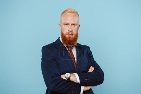 Photo pour Homme d'affaires barbu confiant en costume aux bras croisés, isolé sur bleu - image libre de droit