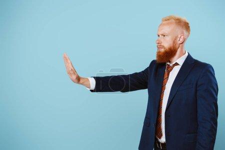 Photo pour Homme d'affaires barbu sérieux en costume montrant un panneau d'arrêt, isolé sur bleu - image libre de droit
