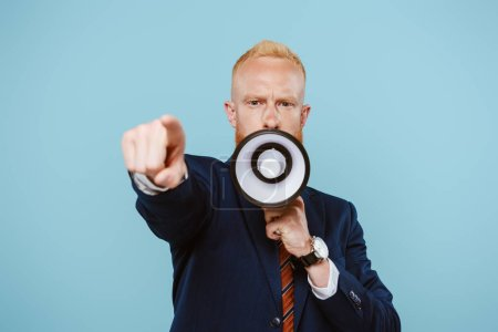 Photo for Angry bearded businessman pointing and screaming into megaphone, isolated on blue - Royalty Free Image