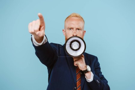 Photo for Angry bearded businessman pointing and shouting into megaphone, isolated on blue - Royalty Free Image