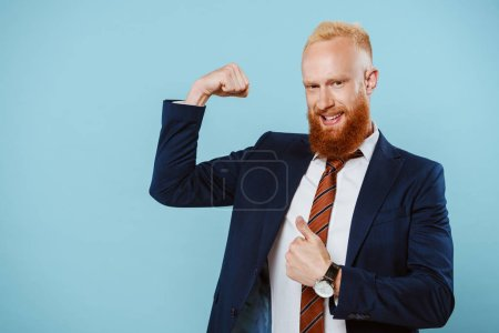 Photo for Smiling strong bearded businessman in suit, isolated on blue - Royalty Free Image