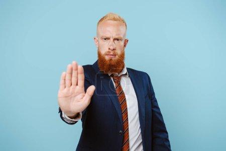 Photo pour Homme d'affaires sérieux en costume montrant un panneau d'arrêt isolé en bleu - image libre de droit