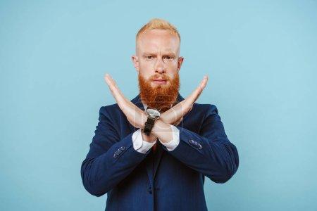 Photo pour Homme d'affaires barbu sérieux en costume ne montrant aucun signe, isolé sur bleu - image libre de droit