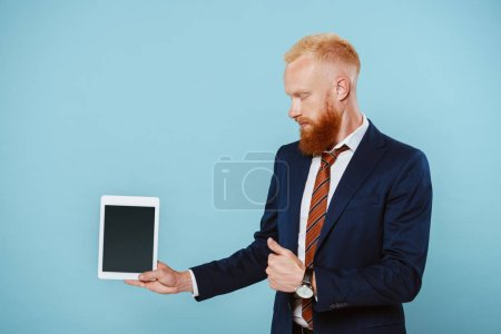 bearded businessman in suit showing digital tablet with blank screen, isolated on blue