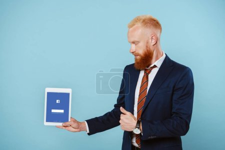 Photo for KYIV, UKRAINE - AUGUST 27, 2019: bearded businessman in suit showing digital tablet with facebook app, isolated on blue - Royalty Free Image