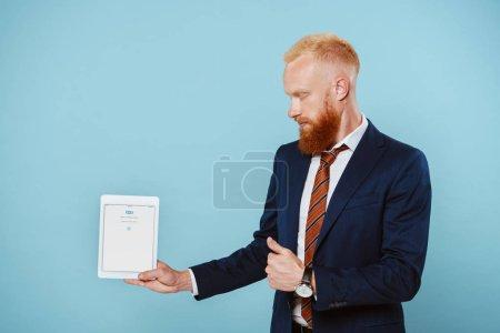 Photo pour KYIV, UKRAINE - 27 AOÛT 2019 : homme d'affaires barbu en costume montrant tablette numérique avec application skype, isolé sur bleu - image libre de droit