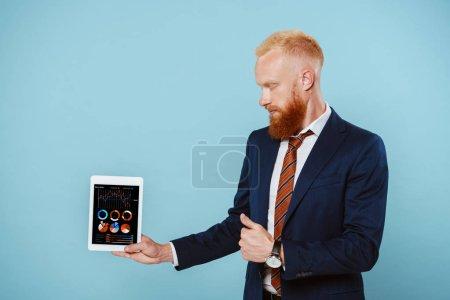Photo pour Homme d'affaires barbu en costume montrant une tablette numérique avec infographie, isolé en bleu - image libre de droit