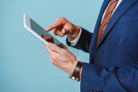 Photo pour Vue recadrée de l'homme d'affaires en costume à l'aide d'une tablette numérique, isolé sur bleu - image libre de droit
