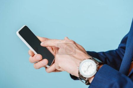 Photo for Cropped view of businessman with wristwatch using smartphone, isolated on blue - Royalty Free Image