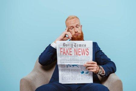 Photo pour Homme d'affaires barbu réfléchi lisant journal avec de fausses nouvelles tout en étant assis dans un fauteuil, isolé sur bleu - image libre de droit