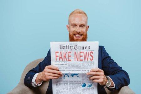 Photo pour Un homme d'affaires barbu souriant lisant de fausses nouvelles dans un fauteuil isolé sur fond bleu - image libre de droit