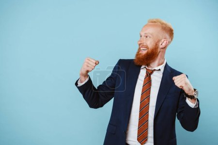 Photo for Cheerful bearded businessman in suit celebrating isolated on blue - Royalty Free Image