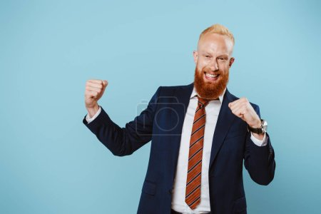 Photo for Cheerful successful bearded businessman in suit, isolated on blue - Royalty Free Image