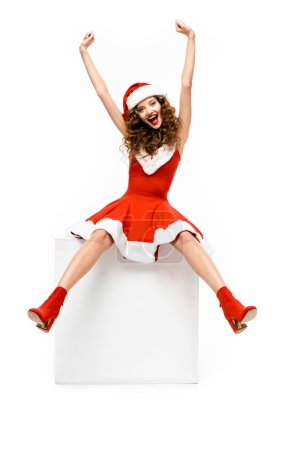Photo for Excited girl in santa costume posing on white cube, isolated on white - Royalty Free Image