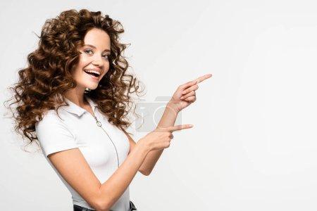 Photo pour Jolie fille bouclée en t-shirt blanc pointant quelque chose, isolé sur blanc - image libre de droit