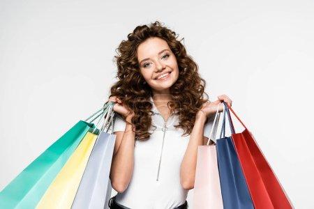 Photo pour Belle fille souriante tenant des sacs à provisions, isolé sur blanc - image libre de droit