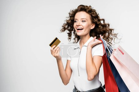 Photo for Happy curly girl holding shopping bags and credit card, isolated on white - Royalty Free Image