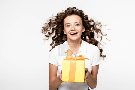 attractive curly girl holding yellow gift box, isolated on white