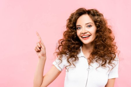 Photo for Beautiful happy curly girl pointing isolated on pink - Royalty Free Image