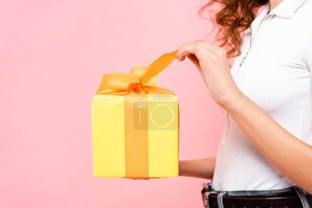 Ausgeschnittene Ansicht von Mädchen mit gelbem Geschenk, isoliert auf rosa