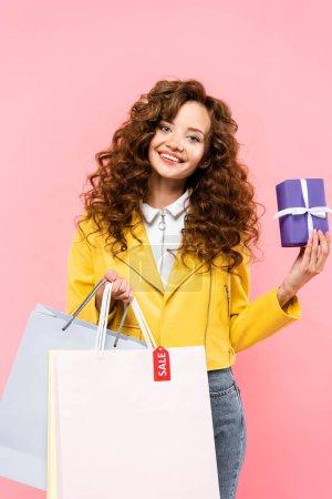 Photo pour Heureuse fille bouclée prenant cadeau de sacs à provisions avec étiquette de vente, isolé sur rose - image libre de droit