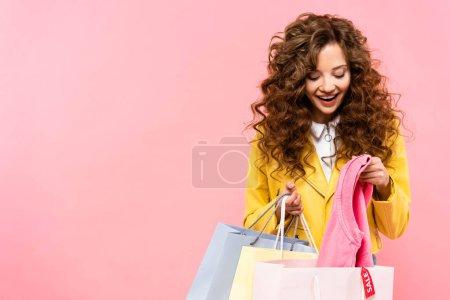 belle fille bouclée heureuse regardant dans des sacs à provisions avec étiquette de vente, isolé sur rose