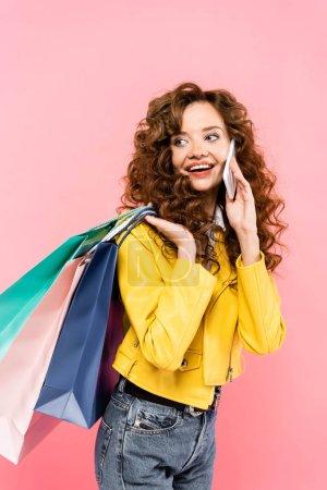 Photo pour Heureuse fille bouclée parler sur smartphone et tenant des sacs à provisions, isolé sur rose - image libre de droit