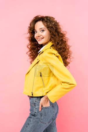 Photo for Attractive smiling curly girl in yellow leather jacket, isolated on pink - Royalty Free Image