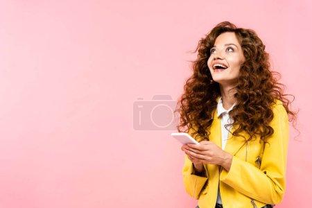 Photo pour Excité fille bouclée en utilisant smartphone, isolé sur rose - image libre de droit