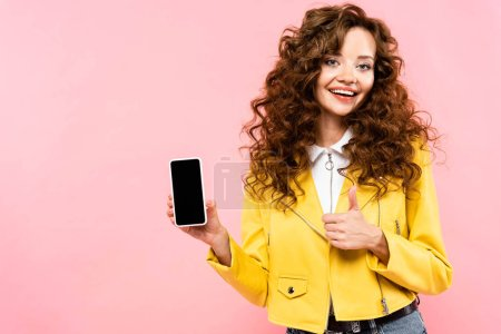 cheerful girl showing thumb up and smartphone with blank screen, isolated on pink