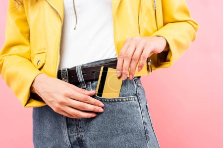 cropped view of girl putting credit card into pocket, isolated on pink