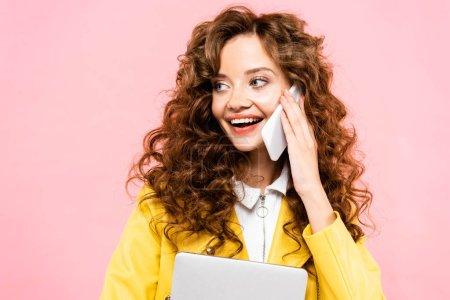 mujer rizada feliz con el ordenador portátil hablando en el teléfono inteligente, aislado en rosa